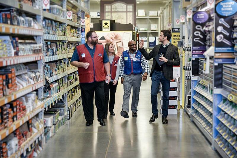Ryan and Lowe's staff walking down a store aisle